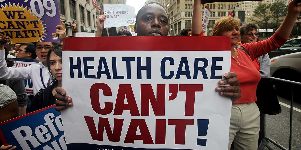 demo with sign saying 'Health Care Can't Wait'